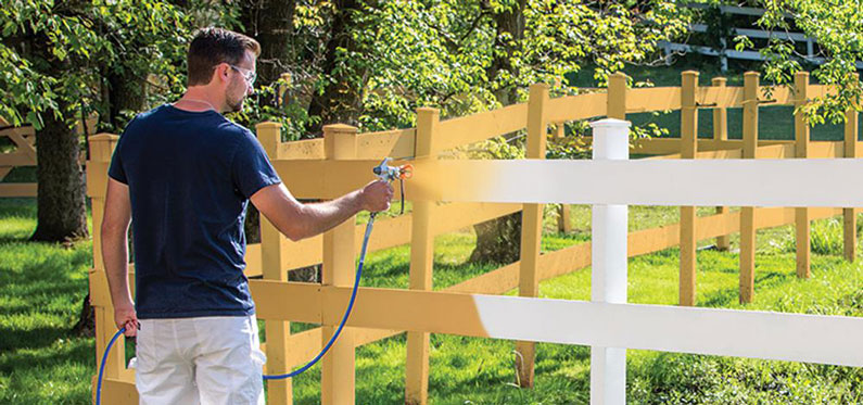 goggled man spray painting white fence yellow