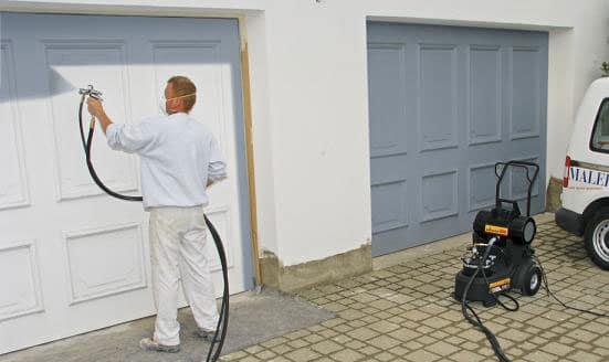 man spray painting garage door blue
