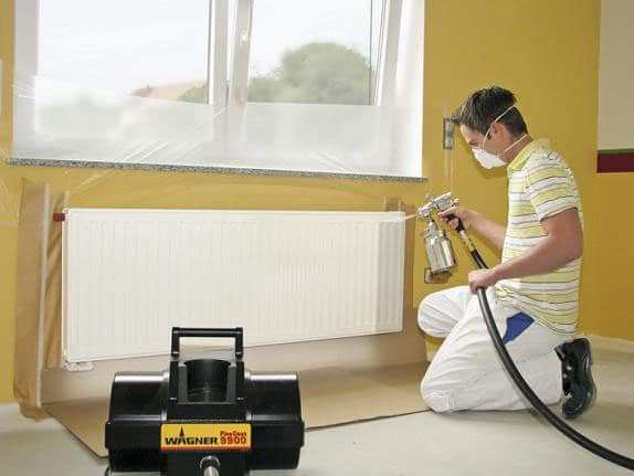 man kneeling to paint radiator white with wagner fc9900 hvlp spray painter