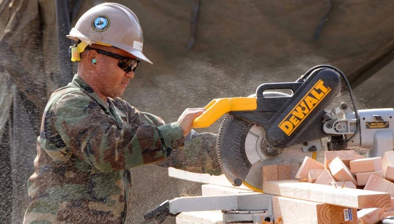 worker with helmet and goggles woodcutting blocks with dewalt miter saw