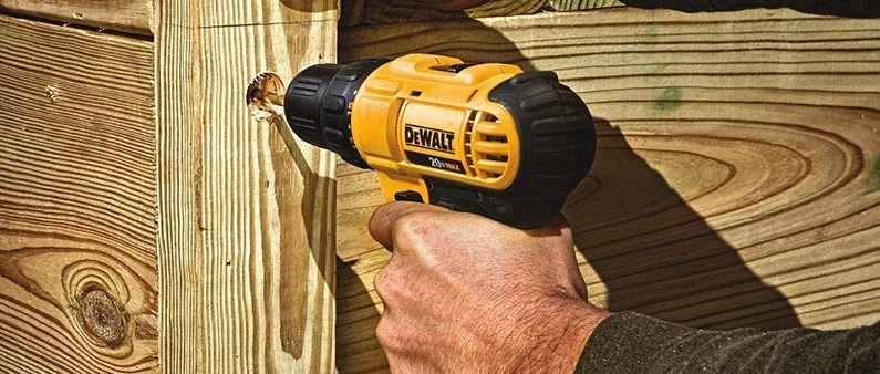 A Man Drilling Hole In The Wood With DeWalt Drill