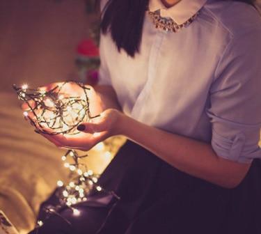 A Woamn Holding Christmas Lights