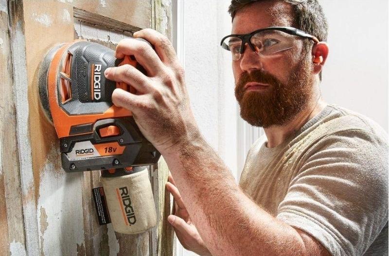 A man working with Ridgid R8606B GEN5X Orbbit Sander