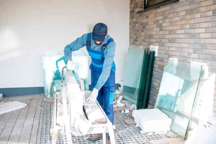 Man cutting tiles with big Tile Cutter on the construction site outdoors