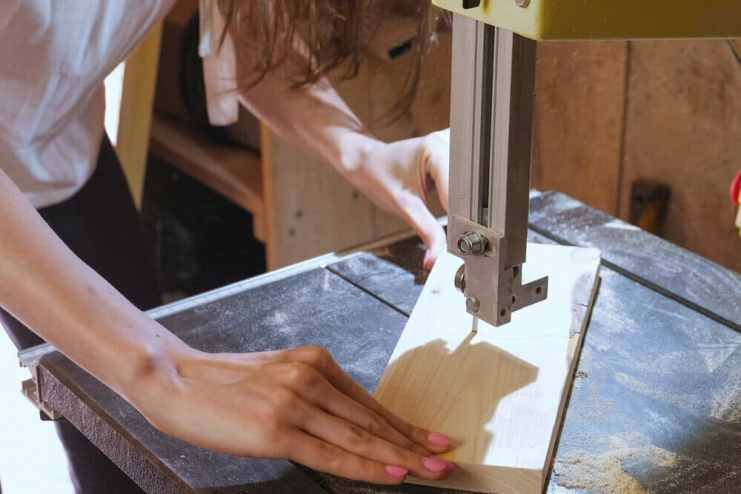 Craftswoman is cutting a wood workpiece with bandsaw