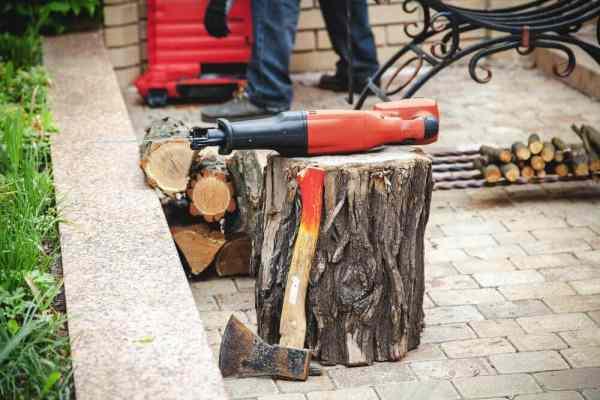 Manual reciprocating saw lying on tree stump