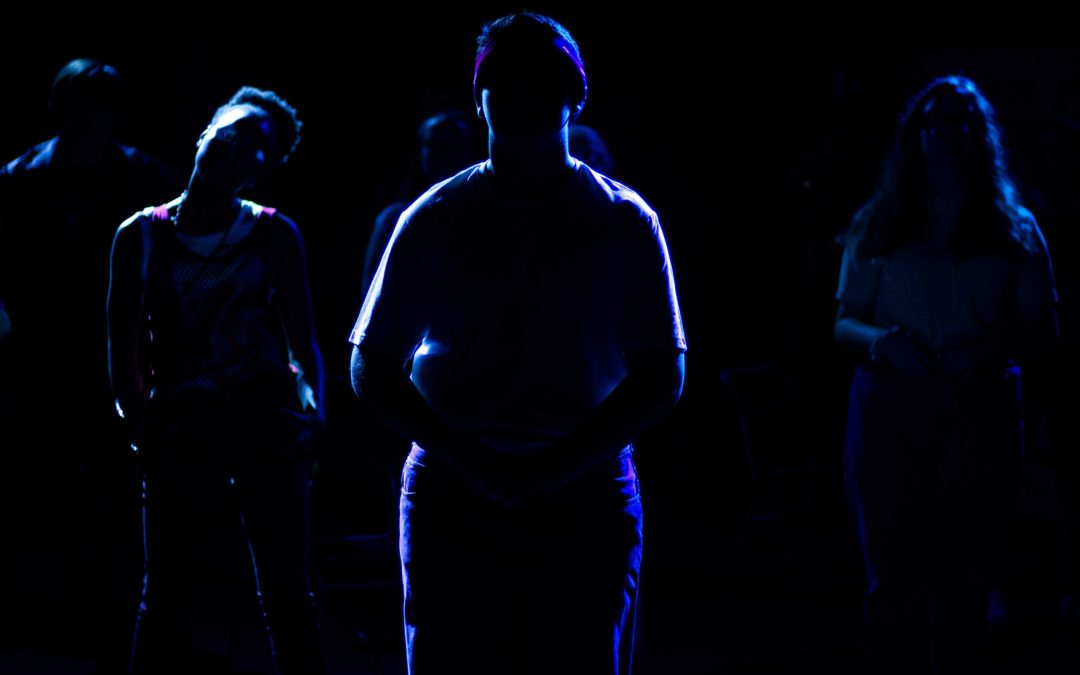 Shapes of young people standing in darkness lined with a faint blue light, staring head on,