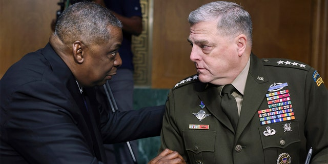 In this June 17, 2021, file photo, Secretary of Defense Lloyd Austin, left, and Chairman of the Joint Chiefs Chairman Gen. Mark Milley talk before a Senate Appropriations Committee hearing on Capitol Hill in Washington. (Evelyn Hockstein/Pool via AP)