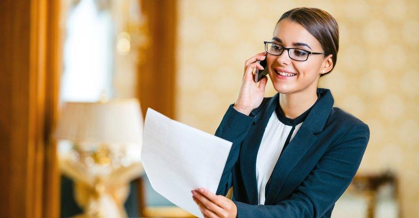 mujer con gafas sosteniendo unos papeles y hablando por telefono