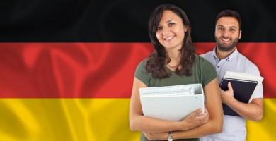 chico y chica sosteniendo una libreta sobre la bandera alemana