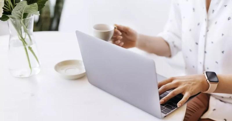 Utilizzando laptop con caffè in mano