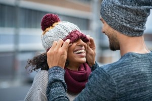 couple having fun outdoor in winter. Young man covering eyes his girl with woolen cap