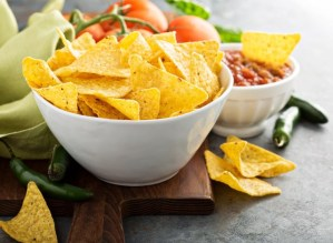 Yellow corn tortilla chips with a bowl of salsa on a cutting board