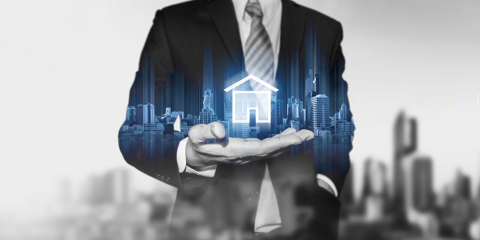 Image of a man holding a hologram of a house and different building in the back ground on the proptech PR agency page.