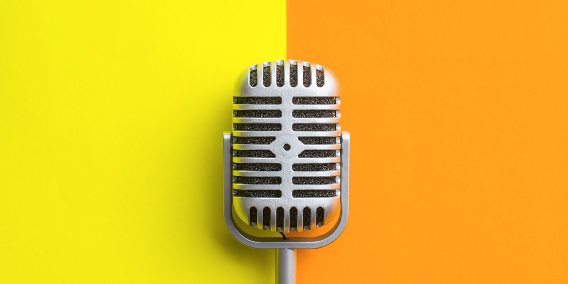 A picture of a silver microphone on a yellow and orange background on the media relations page.