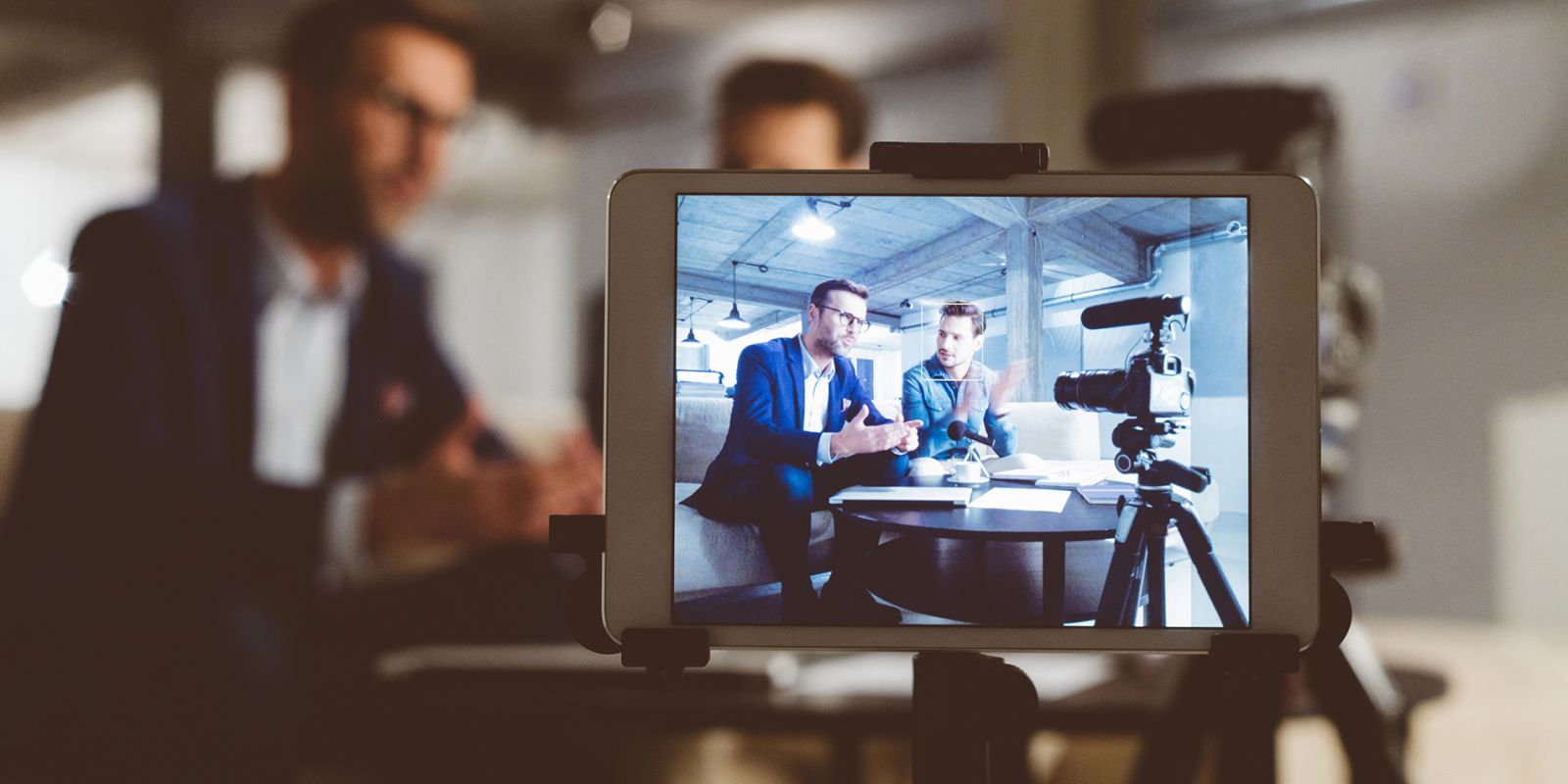 A picture of a video camera focused in on an interview between two men, whilst they sit blurred in the background, on the brand video strategy page.