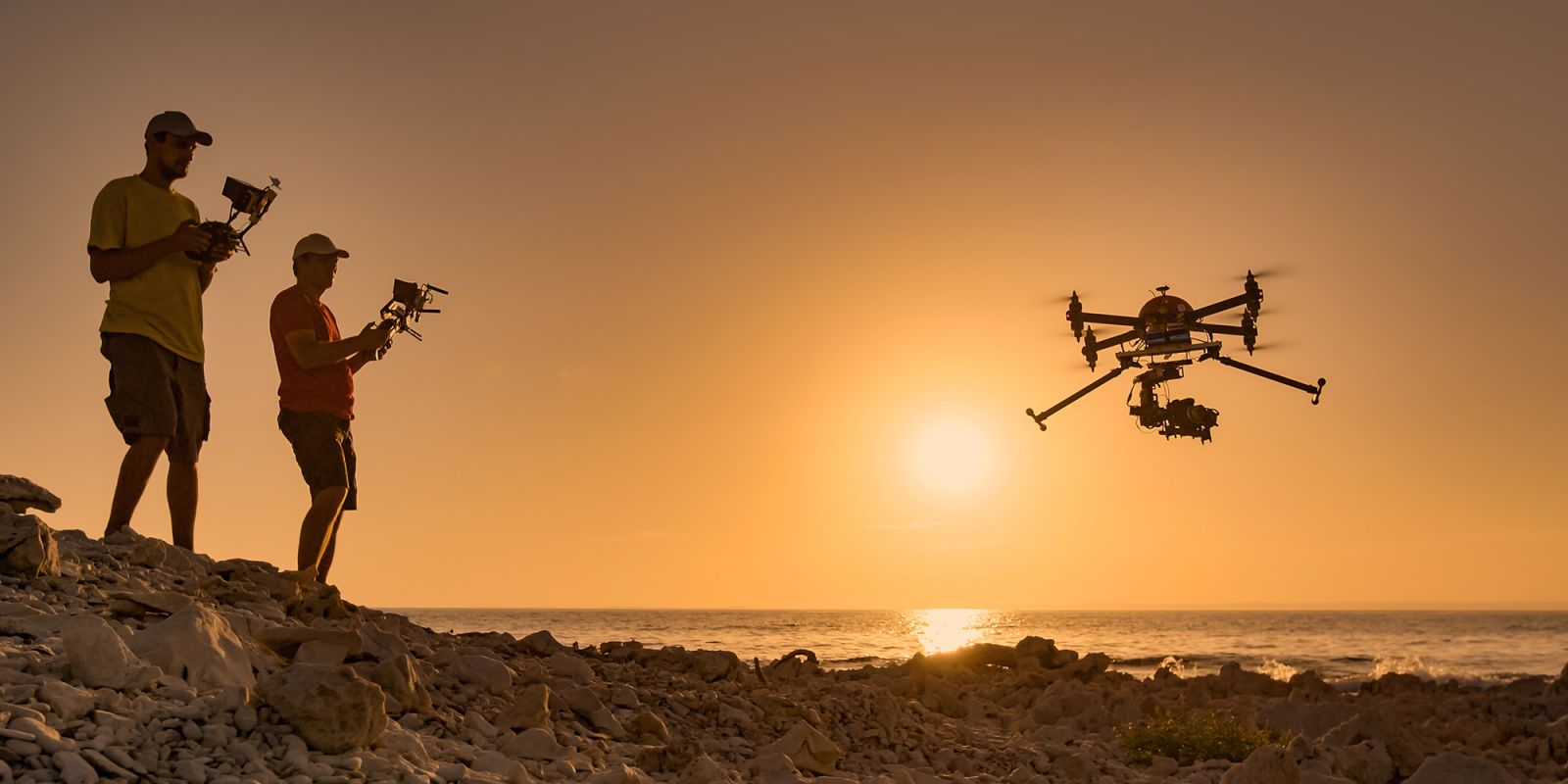 A picture of two mean flying drones on a beach, with the sunset in the background, on the brand video production page.
