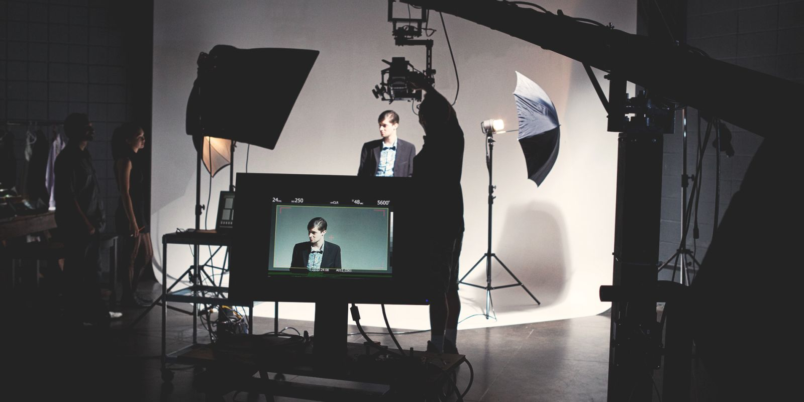 A picture of a guy on set in front of a green screen, surrounded by microphones and video cameras on the HR video production page.