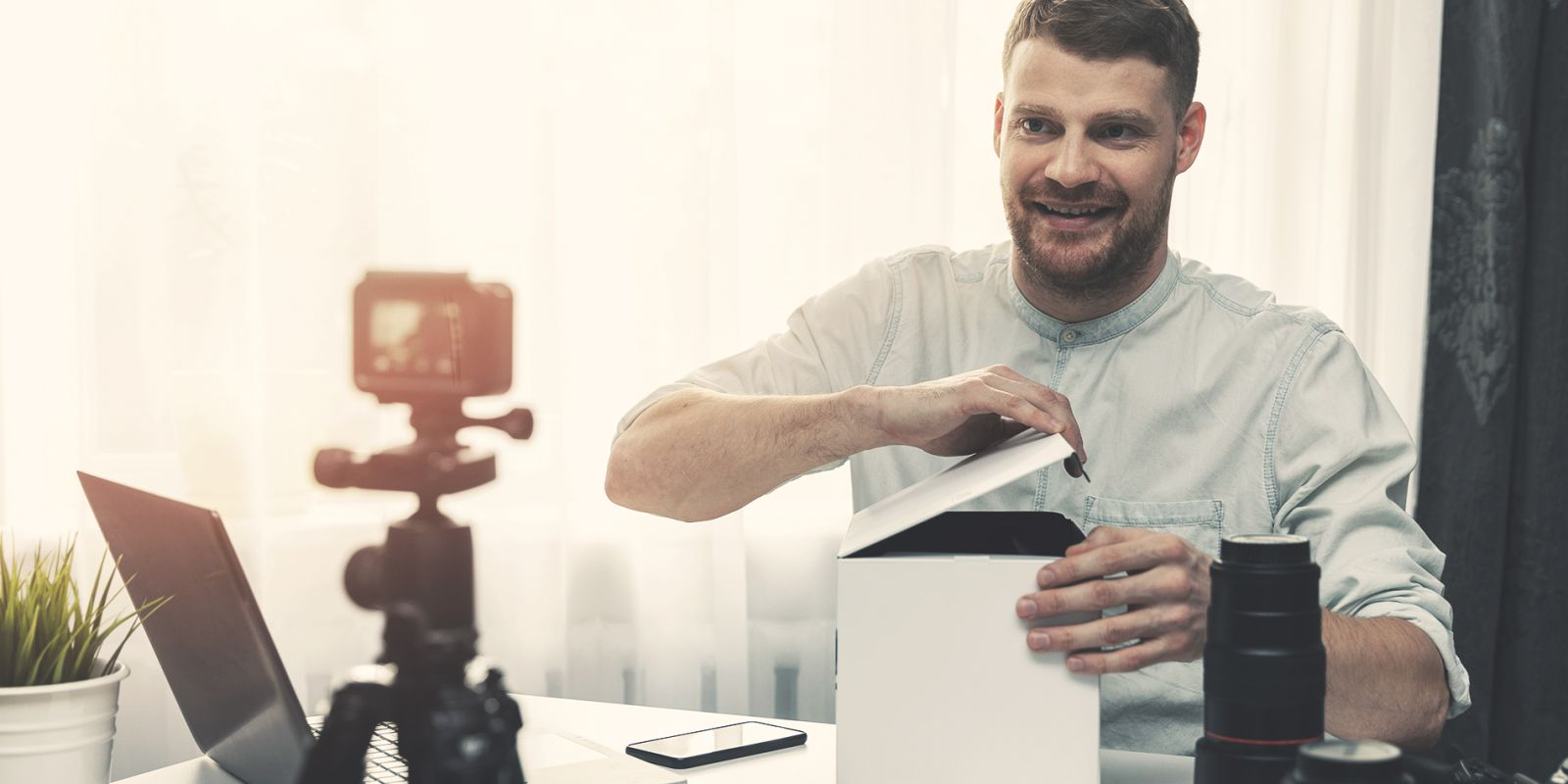Image of a man opening a box whilst filming himself for the product video production page.