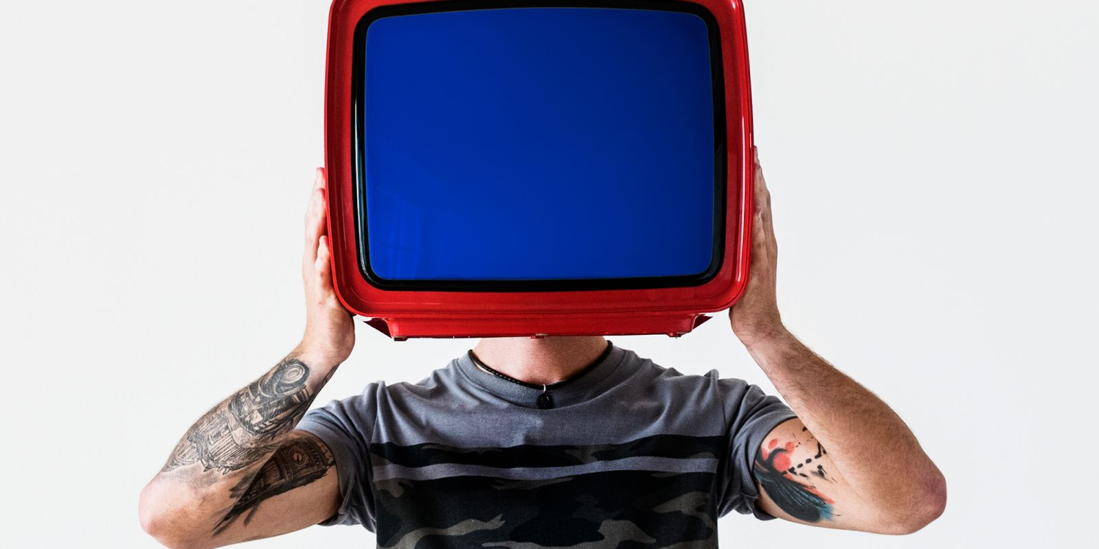 A picture of a man holding a TV screen in front of his face with a bright blue screen on the TV advert production company page.