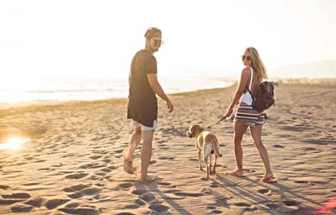 Playas que admiten perros en España - pareja con su perro