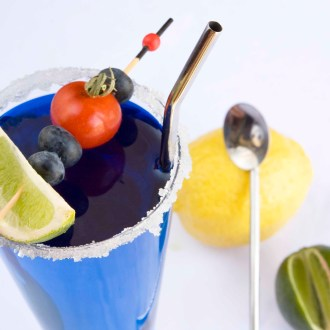 stainless steel straw soop in blue cocktail with blueberries and lime