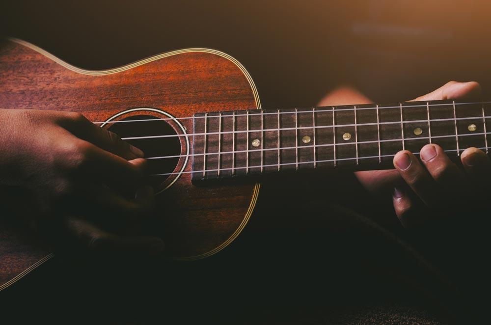 Hands playing acoustic ukulele guitar