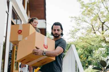 couple carrying boxes on steps while moving out of house