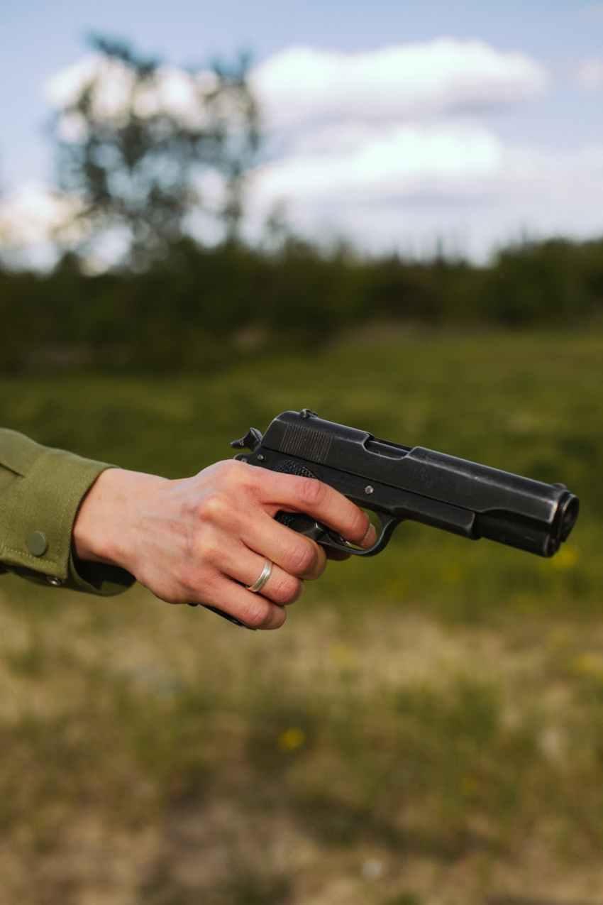 person holding black semi automatic pistol