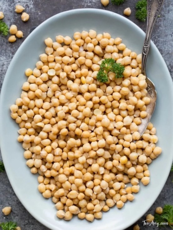 Overhead shot of cooked chickpeas on blue plate with parsley and spoon.