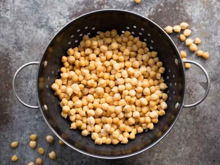Overhead shot of cooked chickpeas in colander on a grey background.