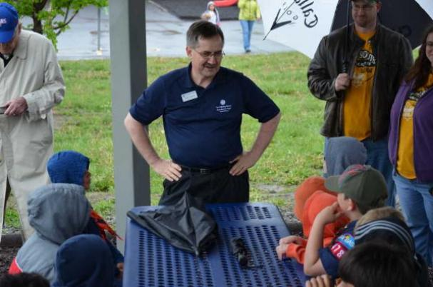 Allan Towle, president and CEO of Fidelity State Bank & Trust, talks to a group of Boy Scouts before they helped him plant a tree at Indian Hills Elementary.