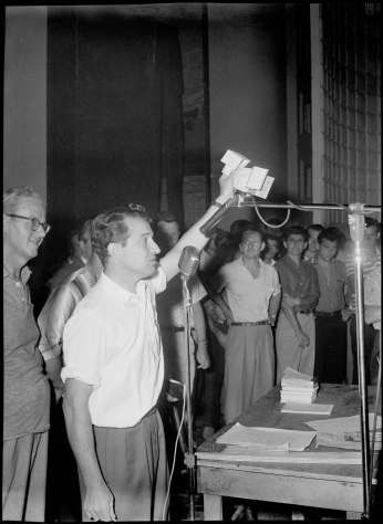 Zanini waving NSF-stamped cheques during meeting at Lansdowne Theatre. Photo by Cooper. August 1, 1960. York University Libraries, Clara Thomas Archives and Special Collections, Toronto Telegram fonds, ASC52274.