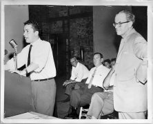 George Petta at the microphone in the Lansdowne Theatre. Gerry Gallagher sits behind him. Photographer unknown. 1961. Archives of Ontario, Charles Irvine fonds.