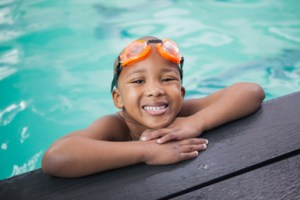 Dark color skin young boy smiling in the pool