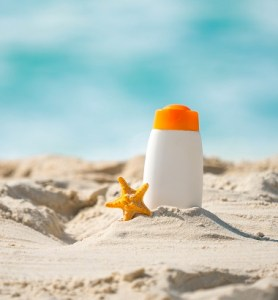 Bottle of sunscreen lotion on beach