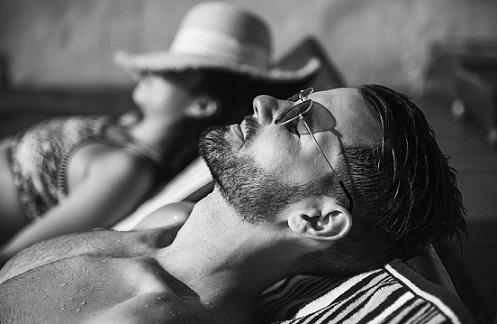 couple sun bathing on beach chairs