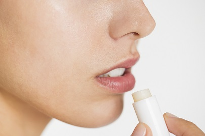 Portrait of white woman doing applying chapstick on lip