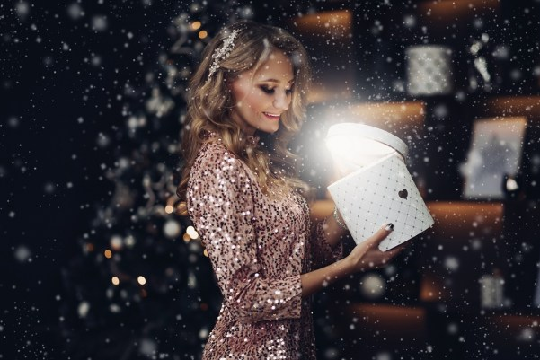 Side view stock photo of gorgeous woman in festive dress opening the box with a Christmas present. She is standing under snowfall. She is looking inside a box with magical light coming from inside.