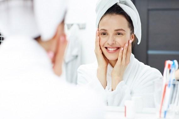 Young woman in bathrobe looking in bathroom mirror