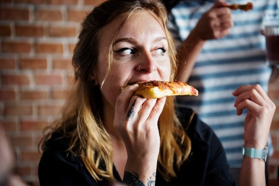 Female eating greasy pizza comfort food