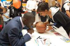 Pops signs a basketball for a fan.