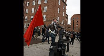 Protester waves anarchist flag on the streets of Copenhagen.