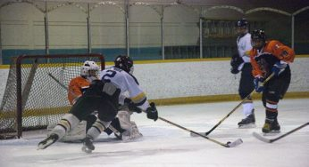 RH King Academy player, Gordie Goode #2, gets a shot off, while falling to the ice. Bendale's Kullen Whalen # 19 defends. Ryan McBride #1, is in net.