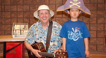 Jim Parker poses after the show with a young boy dressed as a pirate at the Malvern Public Library