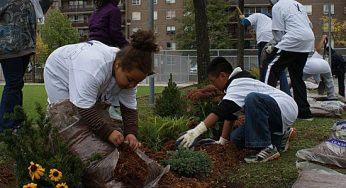 Elysia and Chris spread cedar mulch that will help protect plant roots. Kids from the building at 3181 Eglinton Ave. E. joined members of Toronto Anti-Violence Intervention Strategy (TAVIS) to beautify the building's courtyard, have some fun and build relationships on Saturday.