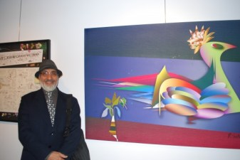 Ranjit Sidhu stands next to his piece, 'My World, My Way,' a mixed media on canvas.