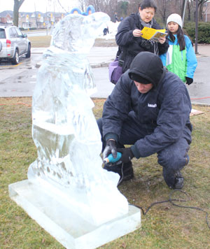 Gresham Bayley of iceculture Inc carves a penguin during Saturday's Winterfest. The sculpture will remain outside of the community centre until it melts.