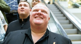 Mayor Rob Ford rides down the Scarborough Town Centre escalator Saturday with media in tow.
