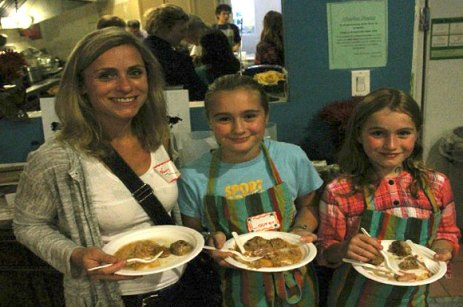 Nancy Kraetschmer (left) and her daughters Lauren (centre) and Katie, of German descent, had a vested interest in this recent Kids Cook To Care community meal. Not only did Lauren and Katie help make the meal, but it featured German food.